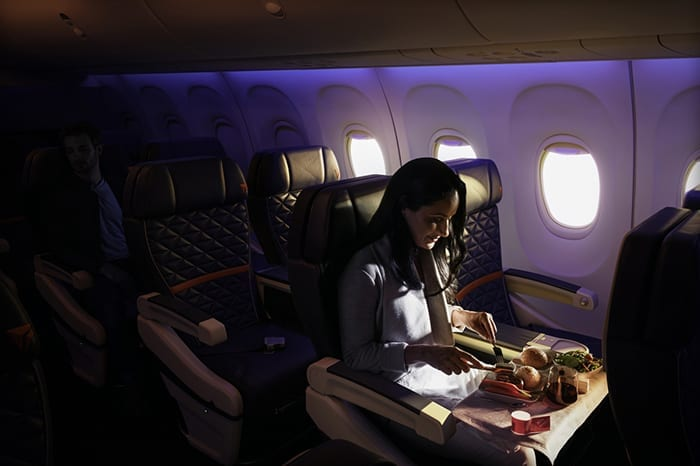 A woman dining and a man sleeping in First Class on a Boeing 737-900ER (739). - These images are protected by copyright. Delta has acquired permission from the copyright owner to the use the images for specified purposes and in some cases for a limited time. If you have been authorized by Delta to do so, you may use these images to promote Delta, but only as part of Delta-approved marketing and advertising. Further distribution (including proving these images to third parties), reproduction, display, or other use is strictly prohibited.